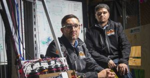 Joaquin Nuno-Whelan '00 and Jonathan Rodriguez mentor students from southwest Detroit in robotics competitions.