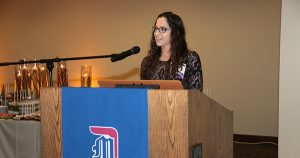 Junior Nursing student Elizabeth Yager speaks to a packed room of Detroit Mercy supporters.