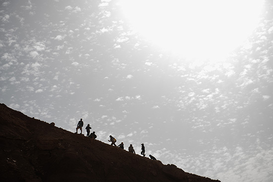Photo of people walking up a large hill with the sun beating down on them.