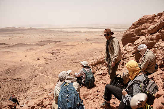 Group of students and professor Nizar Ibrahim on a hill in the Sahara, the vast ness of the desert behind them.