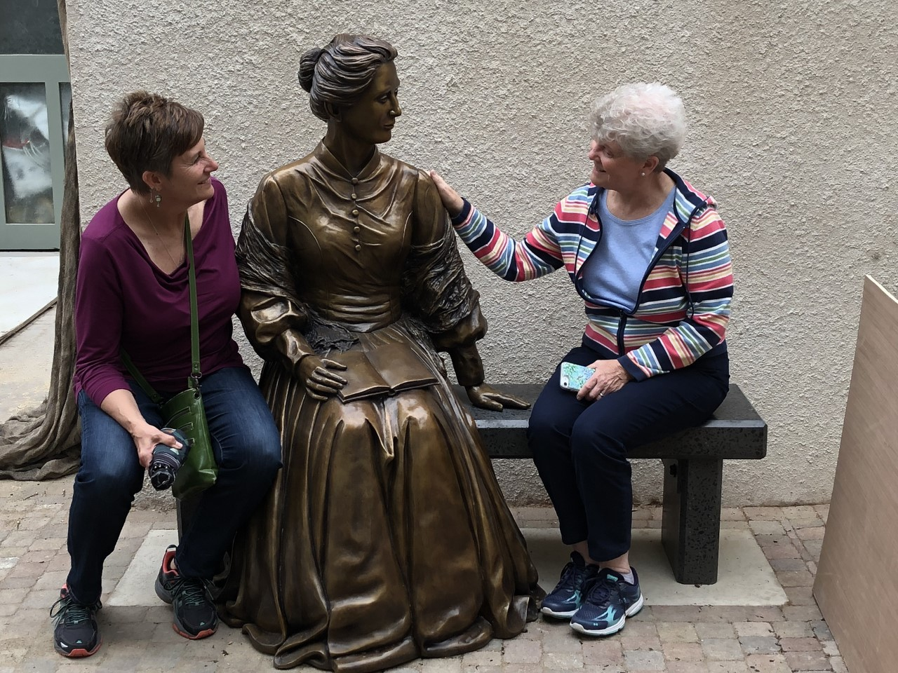 Mary Serowoky, left, and Judy Mouch, RSM, sit with a statue of Catherine McAuley.