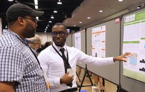 Mitchell Mims discusses his research at a poster presentation.