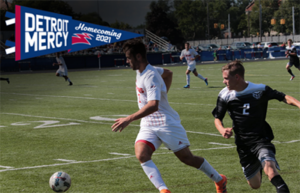 A Detroit Mercy Homecoming 2021 graphic for the men's soccer game vs. Oakland. The Homecoming pennant is in the upper left and the image is of a Titan student-athlete advancing the ball while being chased by an Oakland player.