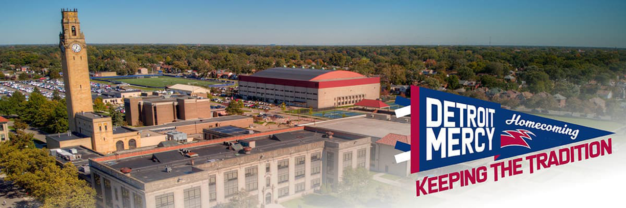 """An aerial photograph of Detroit Mercy's McNichols Campus, with the Detroit Mercy Homecoming """"Keeping the Tradition"""" pennant in the bottom right of the image."""